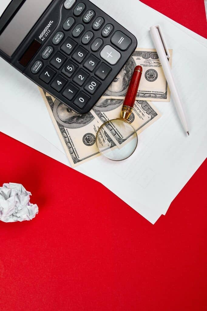 Flat lay or top view of calculator, money dollars and white paper notepad on red background