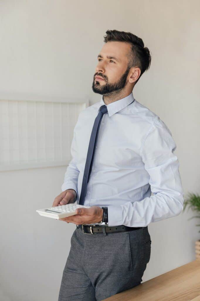 side view of pensive businessman with calculator in hands looking away