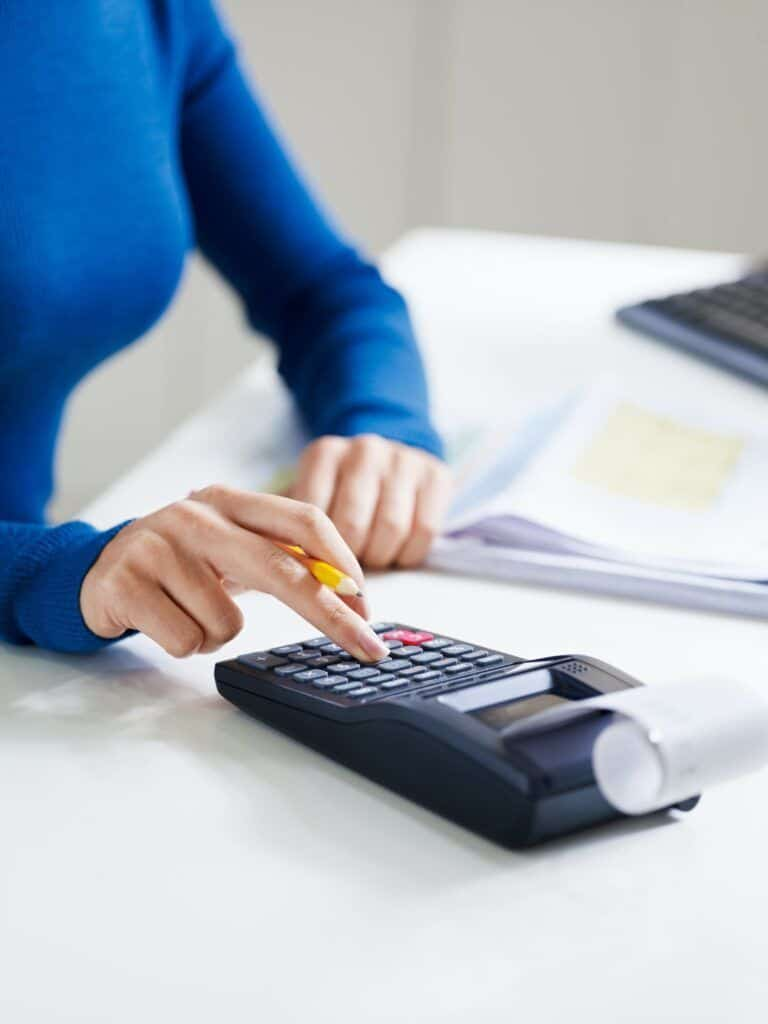 Young Female Secretary Using Calculator In Office
